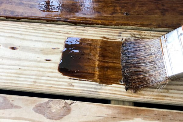 staining-the-deck-with-pine-cone-colored-water-seal-to-protect-it-from-damaging-rain-and-water-to_t20_NxyQQQ